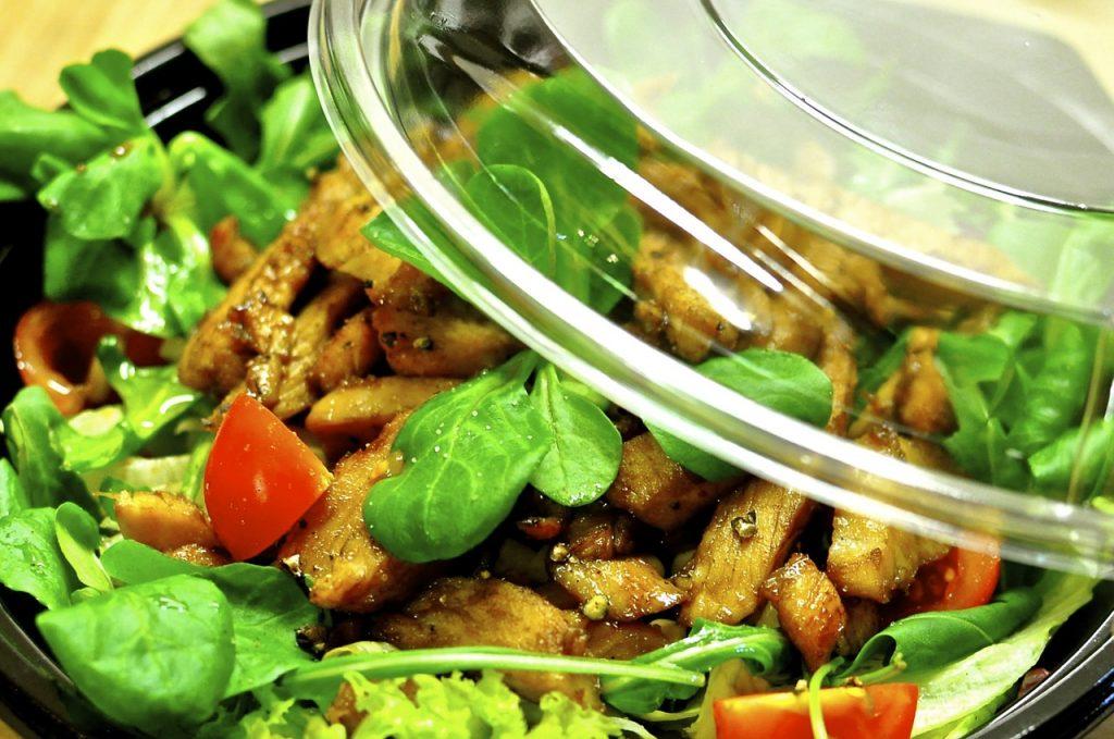 Assiette jetable en plastique contenant une salade et munie d'un couvercle